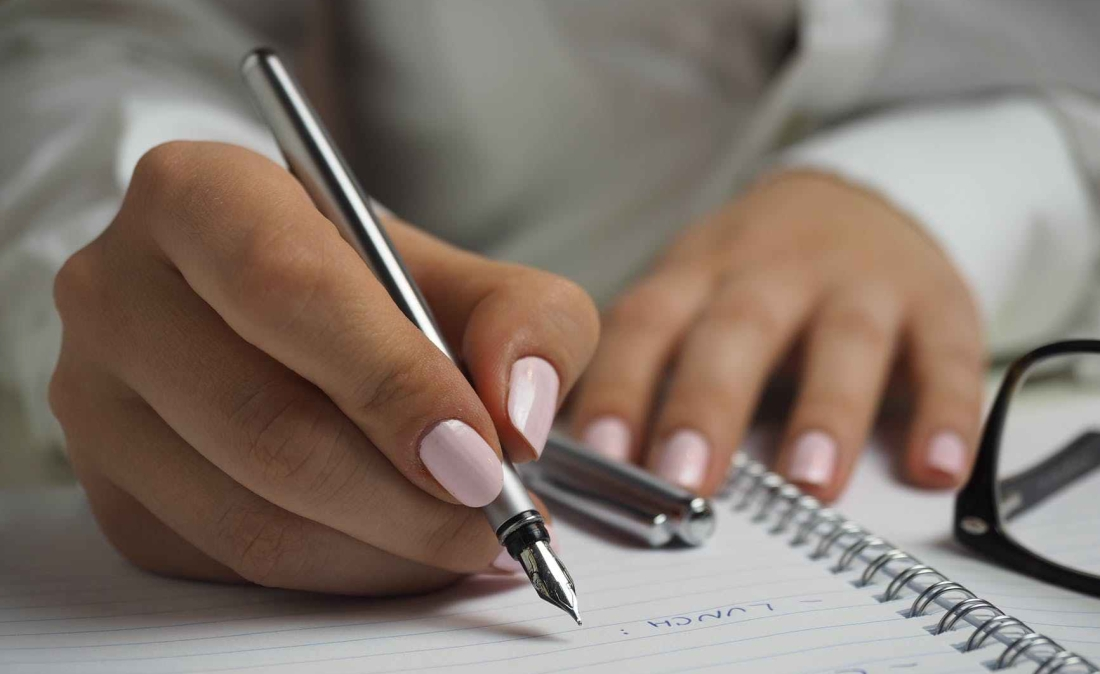 Woman's hands writing with pen on spiral notebook