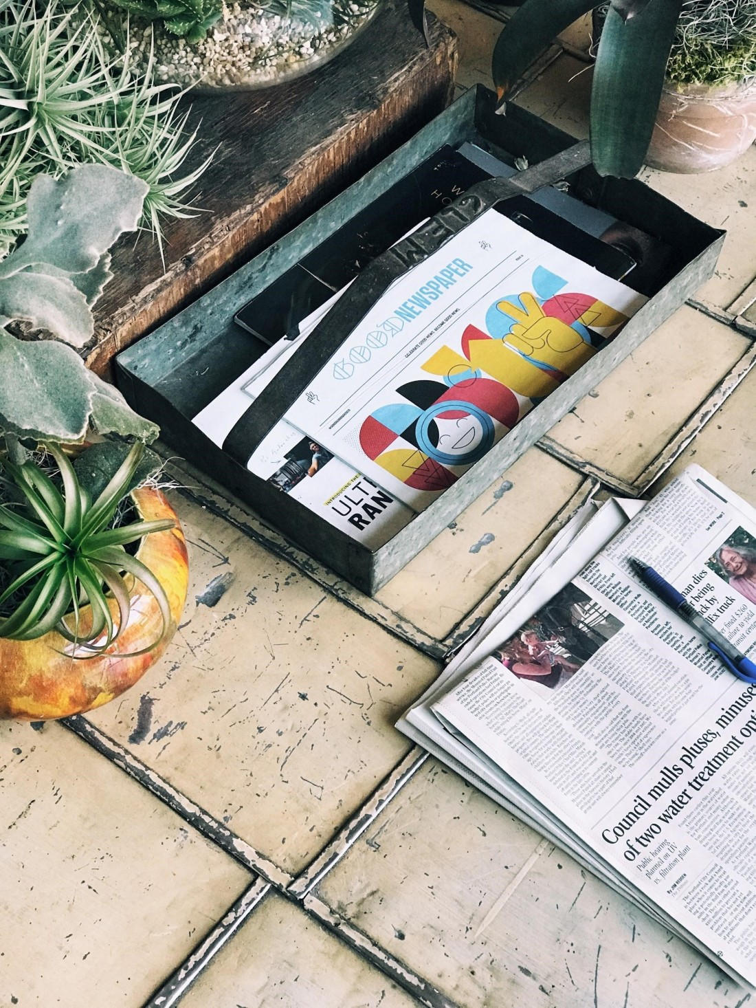 newspapers lying on patio floo with houseplants